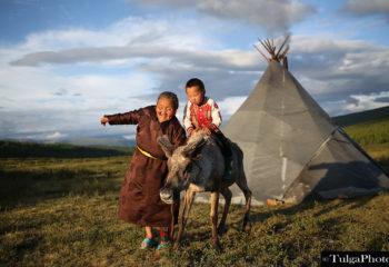 Grandma and boy riding reindeer