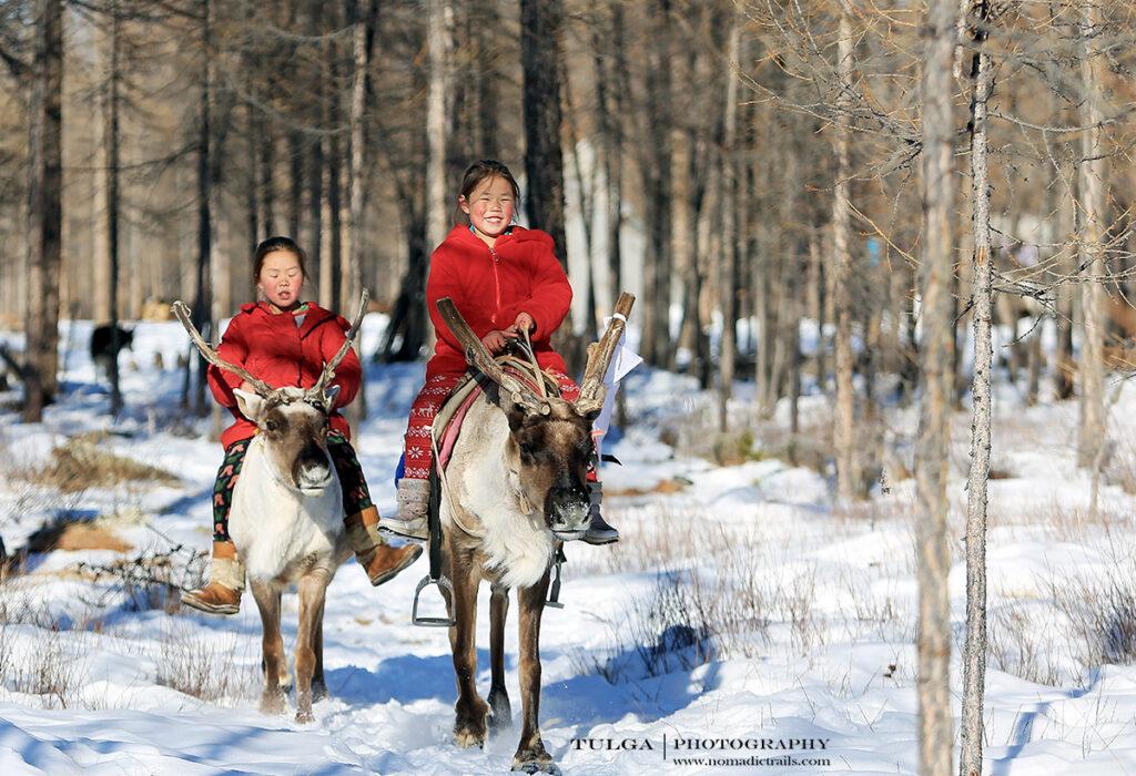 Mongolia reindeer herder girls riding reindeer
