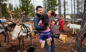 Tulga - Tour Leader, hugging reindeer children