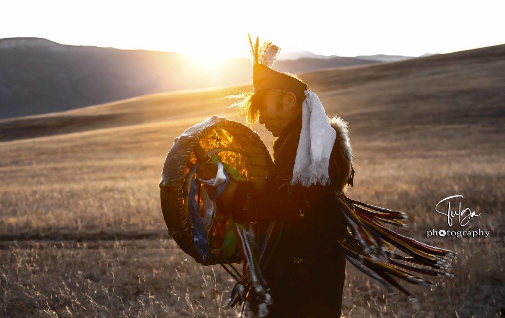 Shaman drumming during sunset
