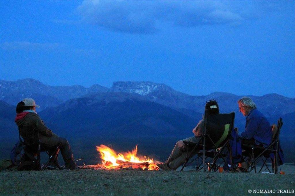 tented camping relaxing near bonfire at night | Horseback riding tips - Nomadic Trails