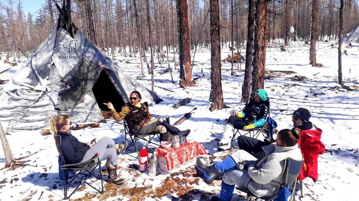 Clients relaxing near tee-pee winter Tsaatan Reindeer herders tour