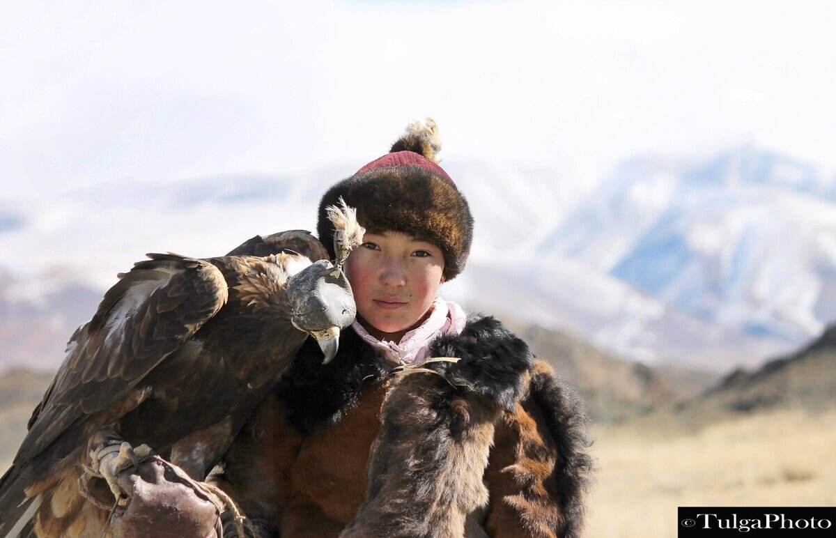 Eagle Huntress with her eagle perched on her arm closeup
